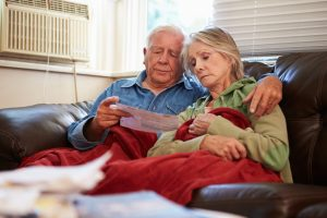 Couple in cold home looking at fuel bill